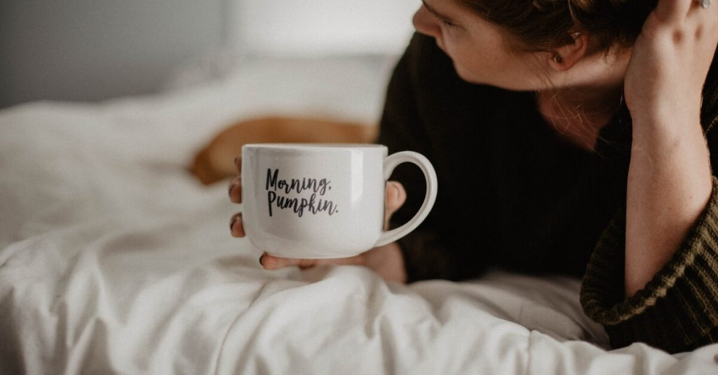 "woman lying on bed with mug that has ""morning pumpkin"" on it"